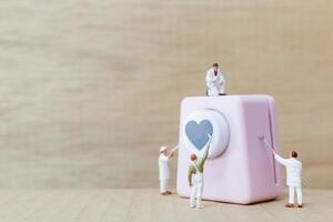 personnes miniatures peignant une poinçonneuse en forme de coeur, concept de la Saint-Valentin photo