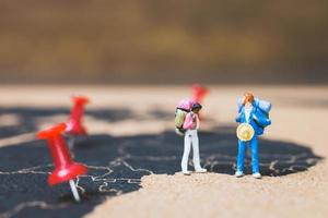 routards miniatures marchant sur une carte du monde, concept de tourisme et de voyage