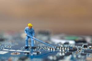 personne miniature travaillant sur une carte cpu, concept technologique photo