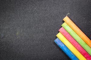 Rangée de craie de couleur arc-en-ciel sur un tableau noir photo