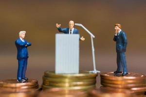 homme d'affaires miniature s'exprimant sur un podium sur une pile de pièces de monnaie, entreprise et concept d'investissement financier