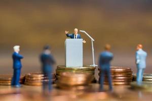 homme d'affaires miniature s'exprimant sur un podium sur une pile de pièces de monnaie, entreprise et concept d'investissement financier photo