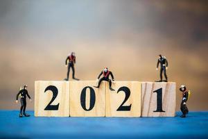 plongeurs miniatures plongeant autour de blocs de bois avec le numéro 2021, concept de bonne année