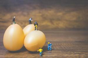 personnes miniatures travaillant sur des oeufs de pâques pour pâques photo