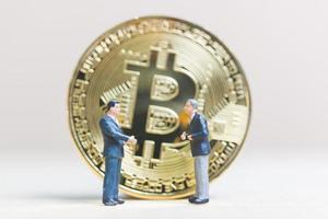 Hommes d'affaires miniatures debout devant une pièce de monnaie crypto-monnaie bitcoin, concept d'entreprise