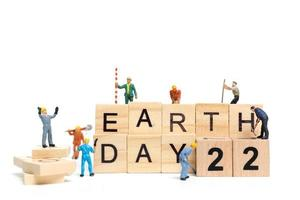 Travailleurs miniatures faisant équipe pour construire le mot jour de la terre 22 sur des blocs de bois photo