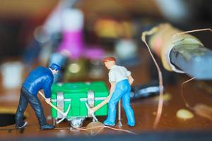 travailleurs miniatures faisant équipe pour réparer les circuits électroniques, concept de travailleurs de la construction photo