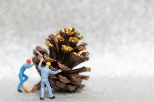 travailleurs miniatures faisant équipe pour préparer une pomme de pin de Noël, Noël et bonne année concept photo
