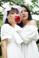 deux femmes avec un gerbera rouge photo