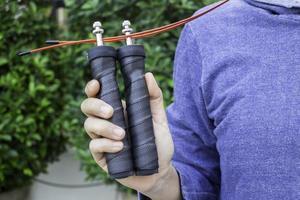main de femme tenant une corde à sauter de vitesse photo