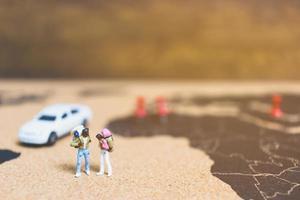 voyageurs miniatures marchant sur une carte du monde, voyageant et explorant le concept du monde