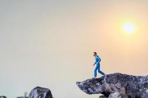 personnes miniatures s'exécutant sur une falaise rocheuse avec fond de nature, concept de santé et de mode de vie