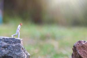 personnes miniatures s'exécutant sur une falaise rocheuse avec fond de nature, concept de santé et de mode de vie photo