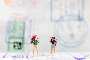 voyageurs miniatures avec sacs à dos marchant sur un concept de passeport, de voyage et d'aventure photo