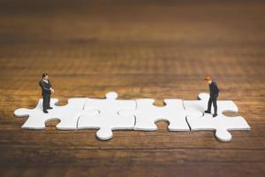 Hommes d'affaires miniatures debout sur des scies sauteuses avec un fond en bois, concept d'entreprise photo