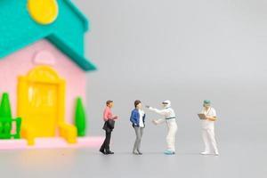 personnes miniatures avec ppe visitant des patients pour un contrôle du coronavirus à la maison, concept de soins de santé