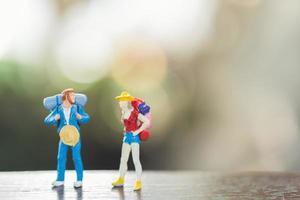 personnes miniatures avec des sacs à dos debout et marche, concept de voyage et d'aventure photo