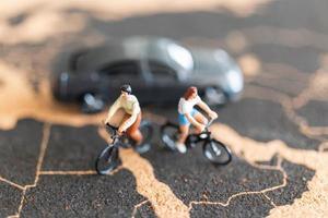 voyageurs miniatures avec des vélos sur un fond de carte du monde