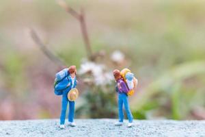 voyageurs miniatures avec des sacs à dos debout sur un concept de route, de voyage et de trekking photo