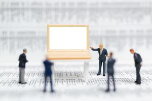 Hommes d'affaires miniatures pensant avec un projet de présentation des investissements sur un ordinateur portable à écran blanc, concept d'entreprise et technologique