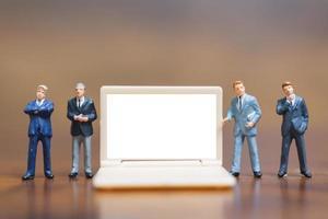 Hommes d'affaires miniatures pensant avec un projet de présentation des investissements sur un ordinateur portable à écran blanc, concept d'entreprise et technologique photo