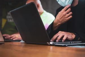 deux personnes parlant au bureau et travaillant sur des ordinateurs portables photo