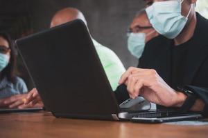 Les gens qui parlent au bureau et travaillent avec des ordinateurs portables avec des masques pour se protéger contre le covid-19 photo