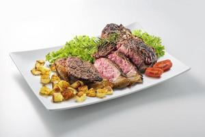 Bifteck d'os fiorentina coupé sur une assiette blanche rectangulaire
