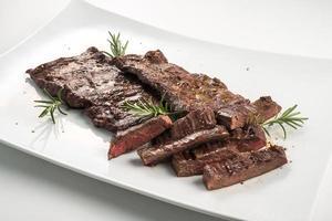 assiette carrée blanche de bifteck de jupe tranché et romarin