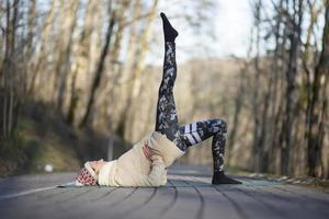 Une jeune femme athlétique effectue des exercices de yoga et de méditation à l'extérieur photo