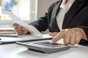 femme d & # 39; affaires portant un costume noir et utilise des calculatrices au bureau photo