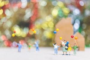 personnes miniatures tenant des ballons dans un parc avec un arrière-plan coloré bokeh, relations familiales heureuses et concept de temps de loisirs insouciant photo