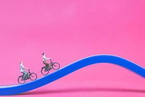 Voyageurs miniatures avec des vélos sur un pont bleu sur fond rose photo