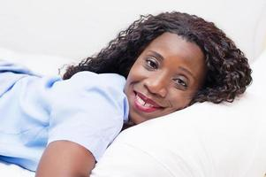 femme souriante détendue allongée sur son lit photo