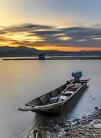 un bateau au bord d'un lac au beau coucher de soleil photo