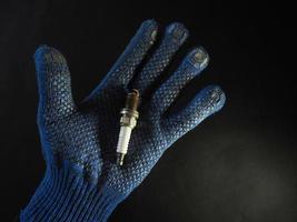 Une bougie d'allumage de voiture défectueuse dans un gant de travail bleu pour homme sur fond noir photo