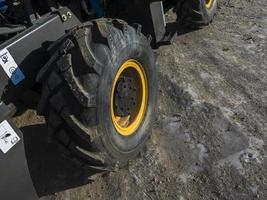 Gros plan d'une roue de chargeur sale avec une grande bande de roulement et une jante jaune photo