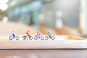 personnes miniatures à vélo sur un pont en bois, concept de soins de santé photo