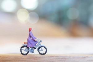 Personne miniature à vélo sur un pont en bois, concept de soins de santé photo