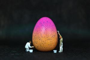 Les gens miniatures peignant des oeufs de Pâques pour le jour de Pâques sur un fond noir photo