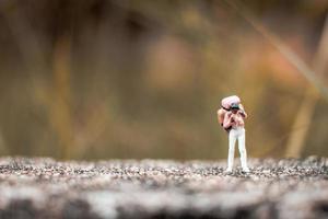 Backpacker miniature debout sur un sol en béton avec un fond de nature bokeh