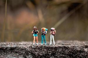 Backpackers miniatures debout sur un sol en béton avec un fond de nature bokeh