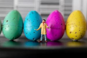 Artiste miniature tenant un pinceau et peignant des oeufs de Pâques pour Pâques