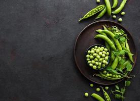 Pois verts dans un bol avec des gousses fraîches sur le fond de béton noir photo