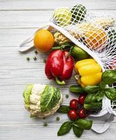 Fruits et légumes frais dans un sac de chaîne écologique sur fond de bois blanc