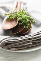 cuillères en bois sur assiette et serviettes en lin décorées de grappes de thym vert photo