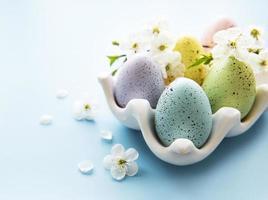 oeufs de pâques dans le plateau d'oeufs et fleur de printemps photo
