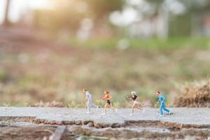 personnes miniatures qui courent sur une route avec un fond de nature, un concept de santé et de mode de vie