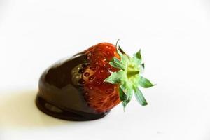 fraises avec une queue trempée dans du chocolat liquide photo