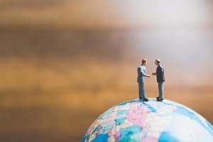 Hommes d'affaires miniatures debout sur une carte du monde globe avec un fond brun